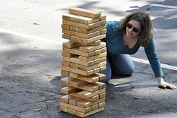 TIMBER!:  Heather Green from San Leandro looks for that perfect block to pull in a giant game of Jenga against Amy McKnight of San Dimas. The two grabbed their spouses and met in the middle for a weekend of fun in San Luis Obispo—which happened to include a stop at CCB's birthday celebration. - PHOTO BY CAMILLIA LANHAM