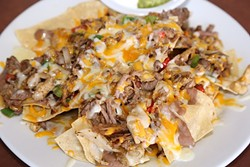 TRIO OF TASTES :  Chicken, carnitas, and carne asada make for a savory, satisfying plate of nachos at Órale Taqueria. - PHOTO BY DYLAN HONEA-BAUMANN