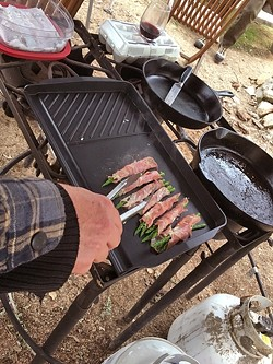 GRUB:  What's a men's campout without decadent foods like these grilled prosciutto-wrapped asparagus with Asiago cheese appetizers? We also ate sausage, bacon, chorizo, and venison. - PHOTO BY GLEN STARKEY