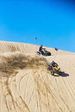 POUNDING SAND:  ATV riders drive around on one of the hills in the Oceano Dunes State Vehicular Recreation Area on Jan. 28. Dust carried by the wind up to the Arroyo Grande/Nipomo Mesa is one of the issues that has plagued the state park. - PHOTO BY JAYSON MELLOM