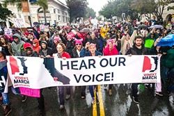 UNITY AND CHANGE:  More than 7,000 marchers flooded the streets of downtown SLO during a downpour on Jan. 21 to participate in the historic Women's March supporting equality and civil rights for all people, which took place in about 600 cities nationwide the day after Donald Trump's inauguration. - PHOTO BY JAYSON MELLOM