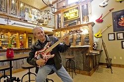 SIPS AND RIFFS:  Gary Kramer sits at his wine tasting room in Paso Robles where rare guitars owned by rock 'n' roll legends like Gene Simmons and Eddie Van Halen hang. - PHOTO BY JAYSON MELLOM