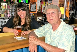 LOCAL HOT SPOT:  Local author Tod Rafferty (right) with Shannon Geyer at Harry's Bar in Pismo Beach, one of the settings for his novel The Pismo Calamity. - PHOTO COURTESY OF TOD RAFFERTY