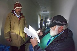 """PERSON-TO-PERSON:  Volunteer Jeff MetCalfe checks Dave Trout into the emergency homeless shelter on Feb. 17 using a headlamp because the power's out. """"This is citizen-to-citizen,"""" MetCalfe says of the coalition's work. """"I'm happy here."""" - PHOTO BY JAYSON MELLOM"""