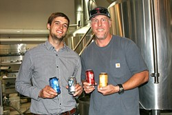 WE CAN DO IT:  From left, SLO Brew Director of Marketing Brian Kerr and Brewmaster Steve Courier showcase their new 23-ounce cans. - PHOTO BY HAYLEY THOMAS