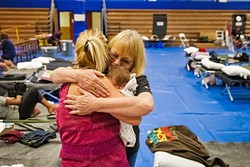 LOVING EMBRACE:  Beth Quaintance from the Salvation Army delivered snacks and hugs to Roxanne Howard and her 6-day-old baby, Xander Earl, at the Red Cross Shelter set up at Flamson Middle School in Paso Robles while the Chimney Fire burned in August. - FILE PHOTO BY JAYSON MELLOM