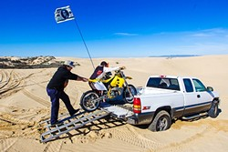 HELPING HAND:   Nick Lalanne helps Cesar Vejar, 20, from Ojai load his broken bike into the back of Lalanne's truck on Jan. 28. Lalanne said it's part of the way things work out on the dunes—people help each other out. - PHOTO BY JAYSON MELLOM