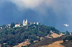 CLOSE CALL:  A tanker helps fight the Chimney Fire from the air on Aug. 21, when the flames came within 3 miles of Hearst Castle. - PHOTO BY JAYSON MELLOM