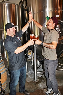 """BEER FIVE:  Central Coast Brewing Co. Head Brewer Brendan Gough (left) and Libertine Brewing Co. Co-Owner/Brewmaster Tyler Clark go for a """"high-five/beer-five."""" - PHOTO BY HAYLEY THOMAS"""