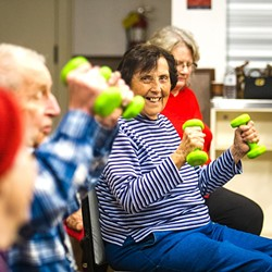 MOVING TOGETHER:  Attendees of the SLO Senior Citizens Center's chair exercise program get to sit, stretch, and exercise in a group. Socializing, singing, and laughter are all part of the program as well. - PHOTO BY JAYSON MELLOM