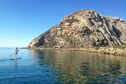 LEARNING THE ROPES:  Clare checks out Morro Rock soon after setting off on our SUPing adventure. - PHOTO BY PETER JOHNSON