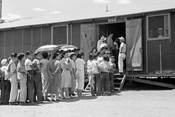RATIONS:  People wait in line for lunch outside the mess hall at the internment camp at Manzanar in 1942. - PHOTO COURTESY OF THE NATIONAL ARCHIVES AND RECORDS ADMINISTRATION