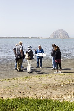 ADULT LEARNING:  Morro Bay State Park docent Faylla Chapman uses her binder full of maps, diagrams, and fun facts to educate people about the history of Morro Bay, changes to the estuary, and all the things that call it home. - PHOTO BY JAYSON MELLOM