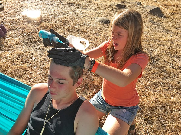 TO DYE FOR Sixteen-year-old Ezra Dickey finds a willing lady friend to apply electric blue hair dye, which he was gifted from an older Live Oak attendee with a blue beard. - PHOTO BY GLEN STARKEY