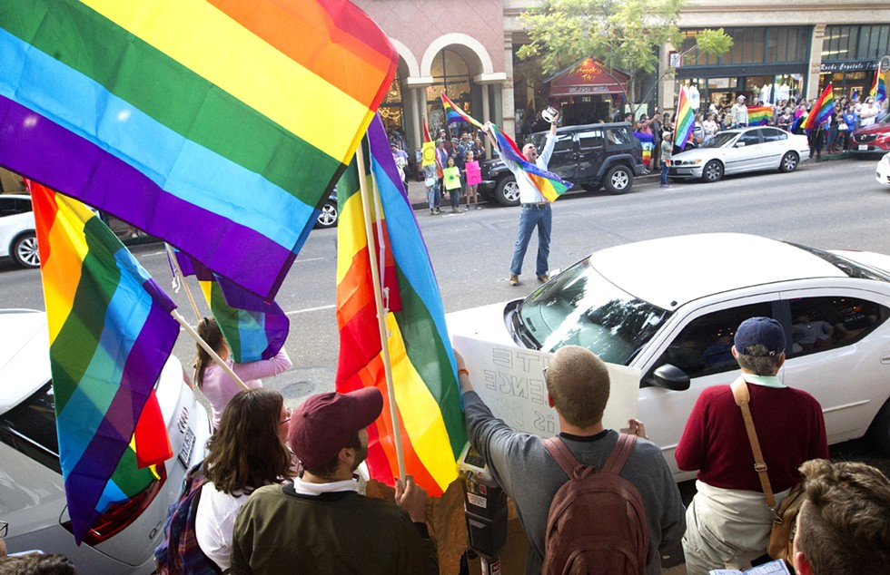 """IN THE STREETS A demonstrator lifts up a Pride flag and yells on Higuera Street in SLO during the """"Show Your True Colors"""" rally in support of the LGBTQ community on June 7. - PHOTO BY JASON MELLOM"""