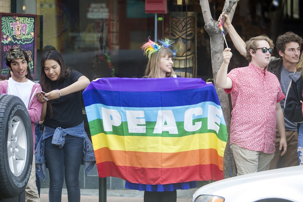"PEACE Countless rainbow Pride flags were displayed at the June 7 ""Show Your True Colors"" rally in downtown SLO. - PHOTO BY JASON MELLOM"