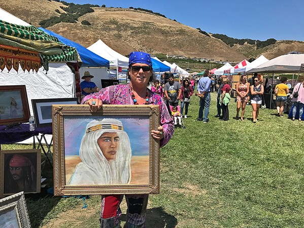 DRESSED TO CHILL Artist E.T. McSparron holds up one of his paintings at Art in the Park. - PHOTOS BY TREVER DIAS