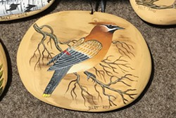 """DRIFTING AWAY Dennis """"Bart"""" Theiler paints birds and other animals on driftwood."""