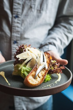 TAP THIS APP Butter lettuce grown at the restaurant's local farm is topped with white anchovies, house Cesar dressing, shaved parmesan, and grilled sourdough. - PHOTO BY HAYLEY THOMAS CAIN