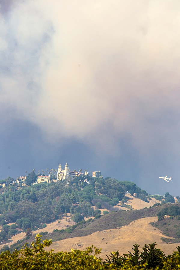 SAVE THE CASTLE An air tanker drops fire retardant near Hearst Castle as the Chimney Fire came within 2 miles of the national landmark. The castle shut down to public tours for several days. - FILE PHOTO BY JAYSON MELLOM