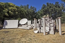 """ROAD LESS TRAVELED Twenty-something artist and musician Dr. Isapony XD built what he calls his """"time machine""""—all sourced from discarded electronics and building materials—in the backyard of his Atascadero rental, where he screens movies and hosts concerts. - PHOTO BY JAYSON MELLOM"""