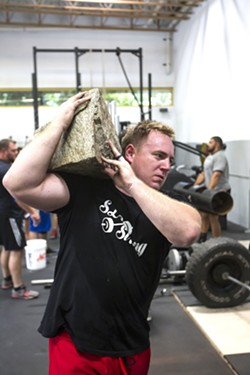 FUNCTIONAL FITNESS SLO Strong co-founder Andrew Wickham carries a large rock at a team workout in June at Headstrong Fit in SLO. - PHOTO BY JAYSON MELLOM
