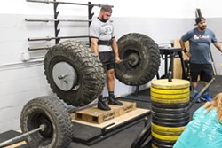 UNCOVENTIONAL Zach Wales, left, lifts a bar with oversized tires on it at Headstrong Fit. - PHOTO BY JAYSON MELLOM