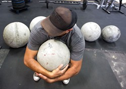 ATLAS Dave LaCaro prepares to lift a 95-pound atlas stone during a SLO Strong workout. - PHOTO BY JAYSON MELLOM