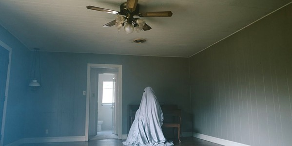 LOSS C, now a sheet-covered ghost, becomes tied to his old house through the vastness of time. - PHOTO COURTESY OF A24