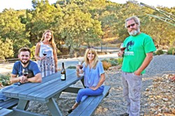 WINE RUNS IN THE FAM Lone Madrone is a family affair. From left, burgeoning winemaker Jordan Collins, Lone Madrone tasting room manager Britta Ray, General Manager Jackie Meisinger, and winemaker Neil Collins. The brother and sister duo founded the winery in 1996, and now Jordan—Neil's son—is helping out the family business. - PHOTO BY HAYLEY THOMAS CAIN