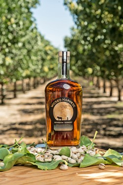 NO REST FOR THE WICKED Farm-to-bottle booze isn't just the stuff of dreams—it's available from Wicked Harvest, owned by Morro Bay residents Jim and Gloria Zion. The couple creates this unique pistachio-infused bourbon whiskey using nuts from their own California Valley fields. The spirit is aged in merlot barrels and distilled in Kentucky. - PHOTO COURTESY OF WICKED HARVEST