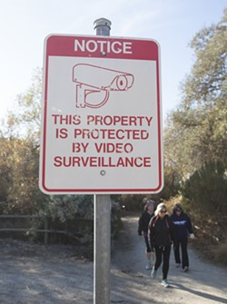 ON CAMERA A sign on the Paso Robles River Walk trail warns of surveillance cameras. - PHOTO BY JAYSON MELLOM