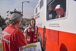 RED CROSS RESPONSE Red Cross Response Vehicles become focal points in disaster-stricken neighborhoods where neighbors regroup, collect water or snacks, and receive breathing masks. - PHOTO BY DERMOT TATLOW COURTESY OF THE RED CROSS