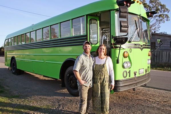 NEXT STOP, FRESH GREENS Kara Strauss, founder and owner of Bloom Microgreens in Los Osos, is the proud owner of SLO County's first functioning mobile micro-farm. Pictured with the neon green school-bus-turned-micro-farm is her husband and biggest supporter, Adam, who found the green machine on Craigslist. - PHOTO BY HAYLEY THOMAS CAIN
