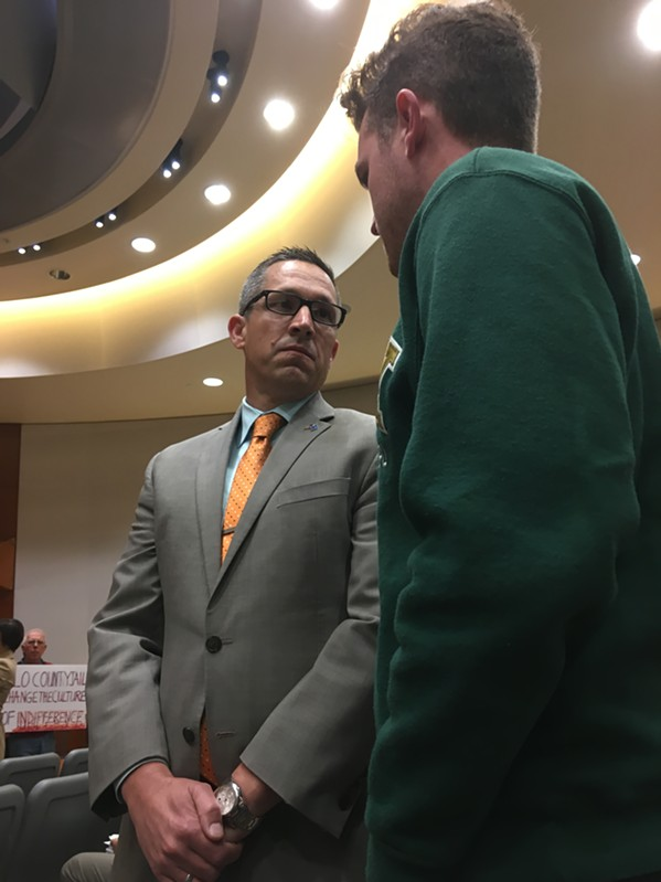 County Chief Administrative Officer Wade Horton asks protestor Matt Klepfer to move the demonstration out of the board chambers. The protestors did not, and the Board of Supervisors adjourned for the morning.