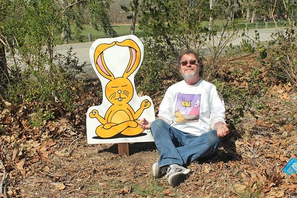ZEN Cartoonist Leigh Rubin relaxes with his creation Lounging Bunny at the SLO Botanical Garden. - PHOTO COURTESY OF LEIGH RUBIN