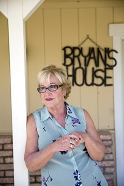 FINDING MEANING Sandy Wortley stands in front of Bryan's House, a residential treatment facility for women struggling with substance abuse. Wortley runs the home that she named after her son, Bryan, who died in 2010 after struggling with an opioid addiction. - PHOTO BY JAYSON MELLOM