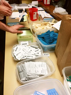 HARM REDUCTION Volunteers at the SLO Bangers Syringe Exchange prepare clean needles and other supplies to give away to drug users in order to help prevent the spread of wounds and diseases. - PHOTO COURTESY OF LOIS PETTY