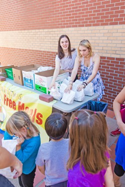 GIVING OUT FREE MEALS San Luis Obispo High School juniors (right to left) Davan Murphy and Ruby Houghton offer free meals to kids that have participated in the summer programs offered at the San Luis Obispo County Library. - PHOTO BY JAYSON MELLOM