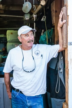HOIST MASTER Dockworker Howie Kennett helps unload fishing vessels and operates an icehouse on Olde Port pier. - PHOTO BY JAYSON MELLOM