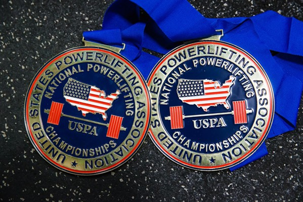 LOST AND FOUND After her powerlifting medals were destroyed in a house fire in July, Juarez had some of them remade by the U.S. Powerlifting Association, including these two for first place and best lifter at a competition. - PHOTO BY JAYSON MELLOM