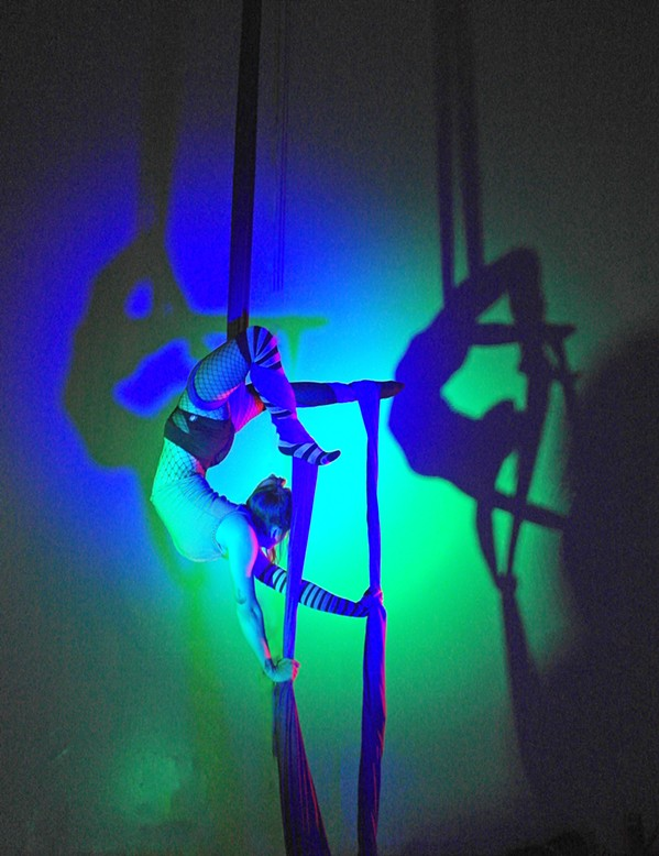 CREEPY CRAWLY Nikki Pesce, an aerialist at Levity Academy, contorts and arches her back while hooking onto the aerial silks. - PHOTO COURTESY OF LEVITY ACADEMY