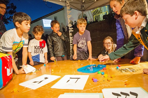 SPIN Kids gather around a table to spin the dreidel in Mission Plaza. The Jewish Community Center of SLO invites the public to participate in Hanukkah festivities like this on Dec. 2. - PHOTOS COURTESY OF THE JCC OF SLO