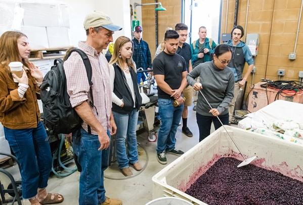 INTRO TO WINEMAKING Alfredo Koch (second from left), instructor and coordinator of the Allan Hancock College viticulture/enology program, leads his class in checking levels of fermentation on grapes in the student winery. - PHOTO BY JAYSON MELLOM