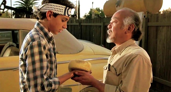 WAX ON, WAX OFF A martial arts master (Pat Morita) agrees to train his 15-year-old neighbor (Ralph Macchio), in The Karate Kid, which screens in celebration of its 35th anniversary at Downtown Centre on March 31 and April 2. - PHOTO COURTESY OF COLUMBIA PICTURES