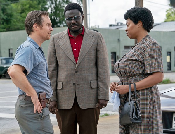 GETTING TO KNOW YOU Klan leader C.P. Ellis (Sam Rockwell, left) and civil rights activist Ann Atwater (Taraji P. Henson, right) learn to respect one another when they participate in a community meeting about school integration led by Bill Riddick (Babou Ceesay, center), in The Best of Enemies. - PHOTO COURTESY OF ASTUTE FILMS