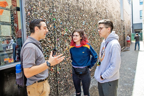 GUM HISTORY Austin Bertucci (left) explains the origins of Bubblegum Alley to two visitors from Phoenix, Arizona. Part of his job as the Downtown SLO ambassador is to engage with tourists about the city. - PHOTOS BY JAYSON MELLOM