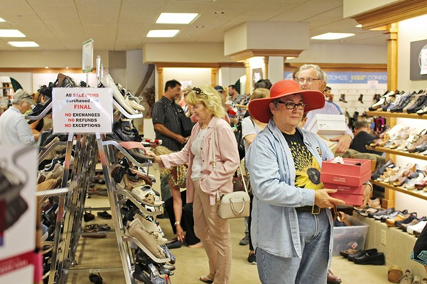 A PIVOTAL STORE LOST Customers take advantage of huge closing sales at Charles Shoes on Aug. 15. The store closed this summer after more than 50 years in business. - PHOTO BY KASEY BUBNASH