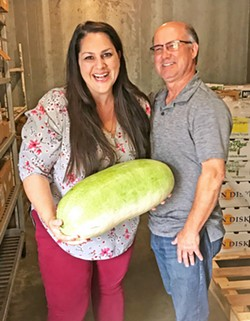 TWO VISIONARIES, ONE MELON FarmSLO founder Jeff Wade (right) stands with Director of Food Services for San Luis Coastal USD Erin Primer as she holds a Charleston Grey melon from a 100-pound box delivered by Robin Song Farms in Templeton. She said she bought them out of their harvest this time around! - PHOTO BY BETH GIUFFRE