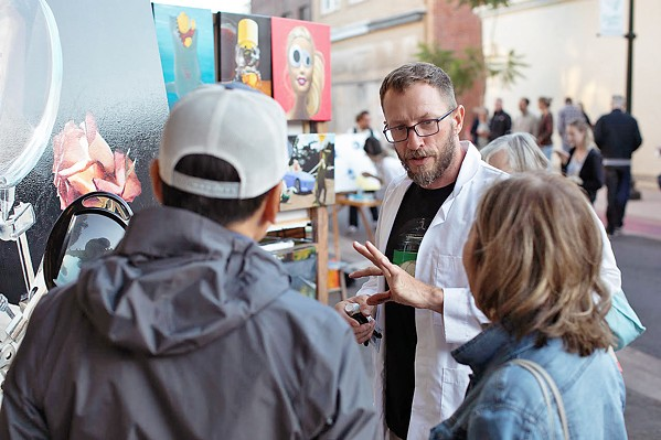 NEW ACCESS POINTS Artist and member of Lamp Light Arts Joshua Talbott speaks with folks at the SLO Farmers' Market whose attention was grabbed by the live painters on Garden Street. - PHOTO COURTESY OF IVAN DITSCHEINER